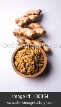 Fresh mashed Ginger / Adrak paste in white bowl with raw ginger over white background