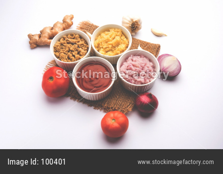 Ginger, Garlic, onion and tomato paste and powder in and raw form. Group of Basic Indian food ingredients over wooden background