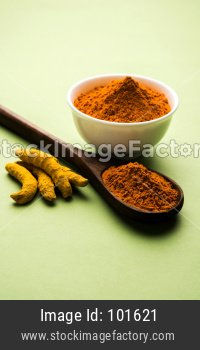 Turmeric or Haldi powder in bowl over colourful background
