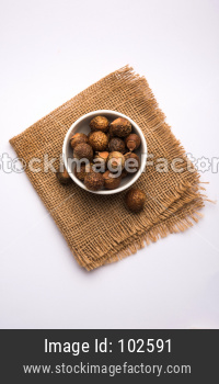Dried ShikAritha or Reetha and oil.  Soap-nuts is used as the main iakai and Reetha OR Soapnut Powder in a bowl, selective focus