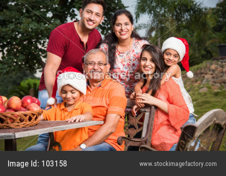 Indian family sitting outdoor and celebrating christmas