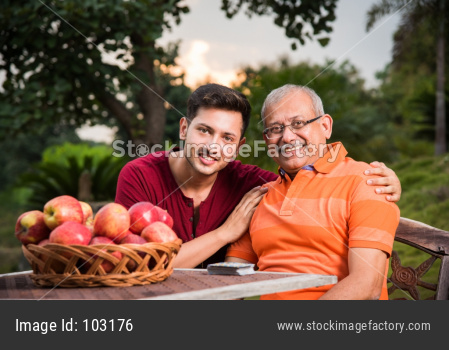 Portrait of Happy Indian/Asian Father and son sitting on lawn chair