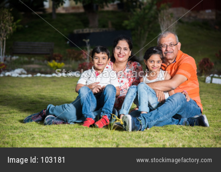 Portrait of Happy Indian/Asian Family - grand parents sitting on Lawn with kids / grandkids, outdoor