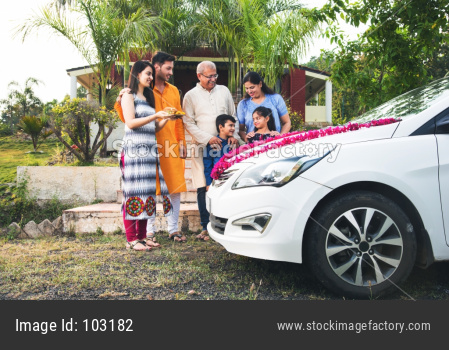 new car buying concept - indian family welcoming new car with puja thali and sweets