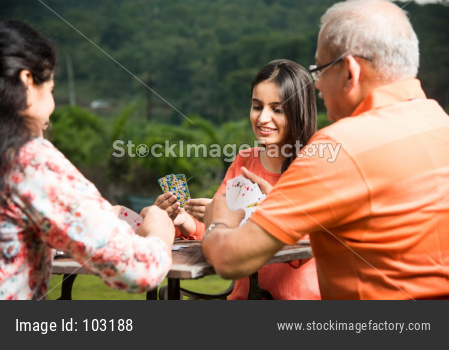 Indian family playing cards while sitting outdoor