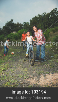 Indian girl learning to ride on bicycle, balancing. Grandma helping her