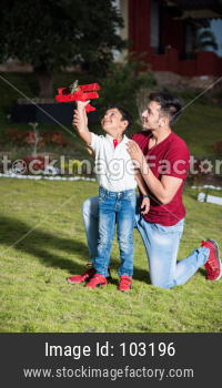 Indian father and son with toy plane, outdoor