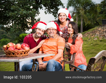 Portrait of Happy Indian/Asian Family celebrating christmas / Xmas while sitting on Lawn chair, outdoor
