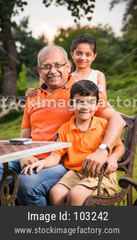Portrait of Happy Indian/Asian Kids and grandfather sitting on lawn chair