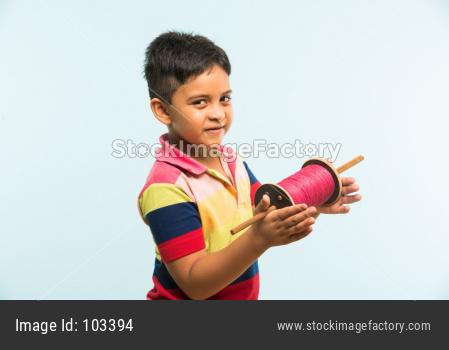 Indian boy holding fikri / spindal / reel on makar sankranti