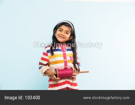 Indian girl holding fikri / spindal / reel on makar sankranti