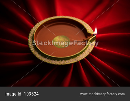 Big Diwali diya over silk cloth or plain background