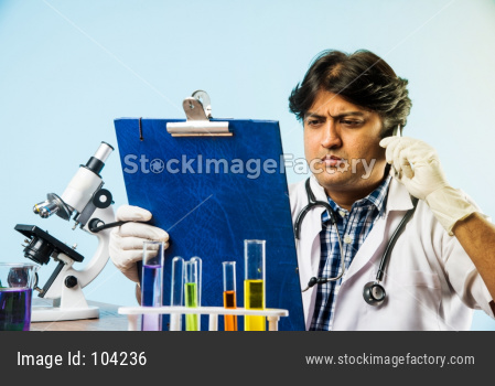 Indian male scientist or doctor or science student experimenting