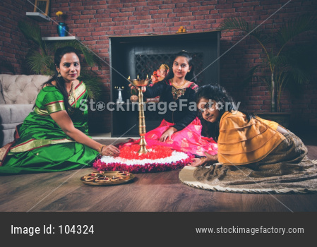 Mother and daughter making flower rangoli and girl lighting diya or samai
