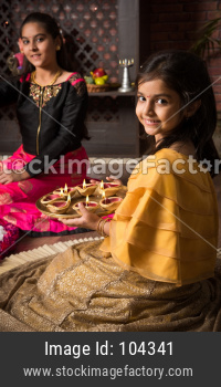 Cute Little girl lighting diya or samai on diwali night