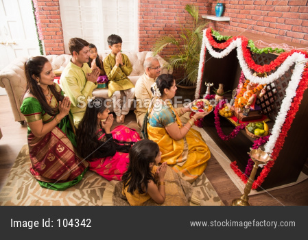 Indian/asian smart family performing Ganesh puja or Aarti at home while wearing traditional wear