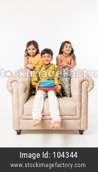 3 indian kids in traditional wear enjoying sweets and gifts on Rakhi or Bhai dooj