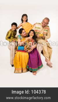 Indian kids with grandparents in traditional wear holding gifts