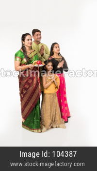 Indian family performing Gudi Padwa puja or ugadi puja with puja thali