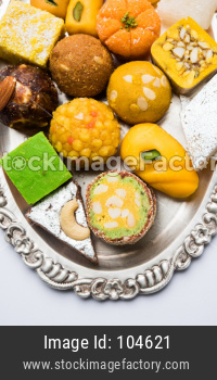 Indian sweets served in silver or wooden plate. variety of Peda, burfi, laddu in decorative plate, selective focu