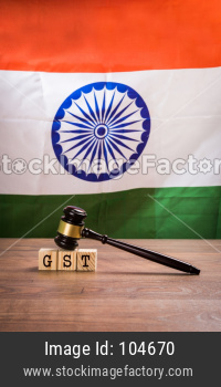 Indian GST Law concept with gavel and wooden blocks with Indian flag in the background