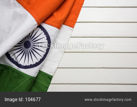 Indian flag with folds over wooden table