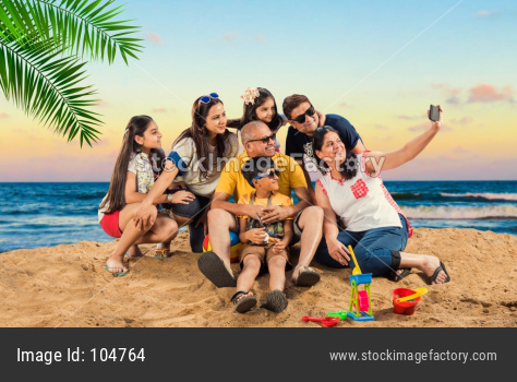 Indian/Asian Family enjoying at beach, posing for picture