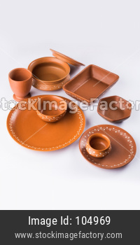 Empty terracotta dinnerware or dining set like plate, soup bowl, serving bowl, glass made up of brown clay, isolated over white