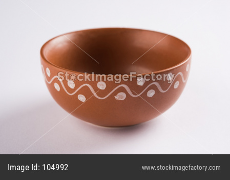 Empty terracotta serving bowl or brown clay soup bowl isolated on white