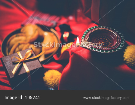 Diwali Sweets OR Mithai, Gift boxes and Crackers arranged over moody background