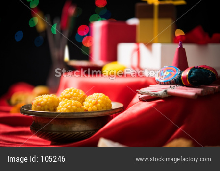 Diwali Diya, Sweets OR Mithai, Gift boxes and Crackers arranged over moody background