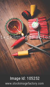 Diwali Diya with Fire Crackers over wooden background. Selective focus