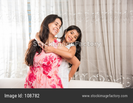 Indian little girl with mother playing indoors
