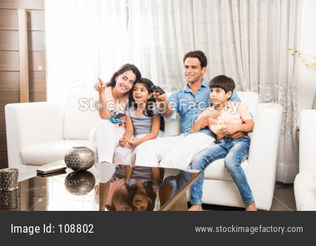 Indian family watching television / Tv while sitting on sofa