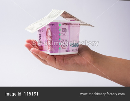 Hand holding 3D Model house using Indian currency