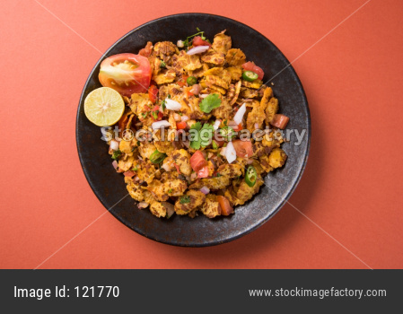 Chana chor garam - Indian roadside spicy chat or snack food, served in a plate or bowl over colourful or wooden background. Sele
