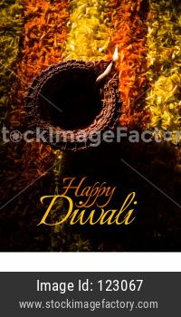happy diwali greeting card showing Clay Diya over flower rangoli