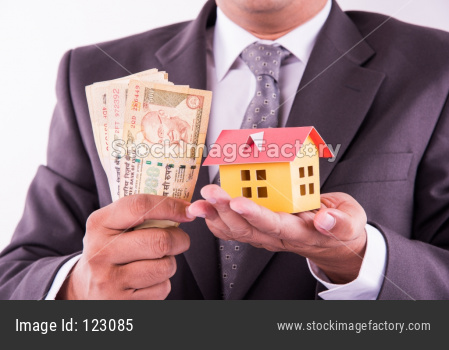 Home buying or real estate in India - Closeup of indian man holding indian Rupees and 3D home model