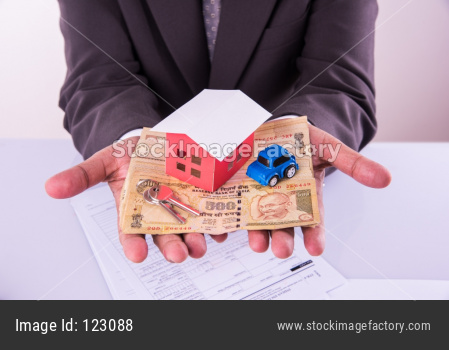 Home and car buying in India - Closeup of indian man holding indian Rupees and 3D home and Car model