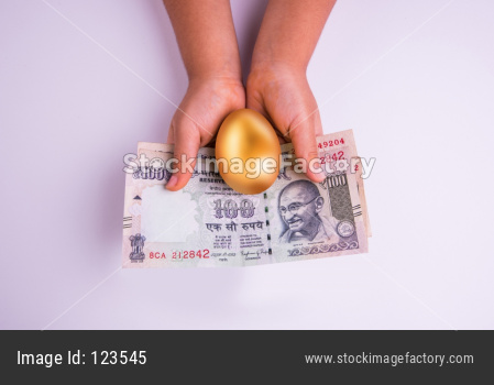 Hand holding indian currency notes or hundred rupee notes and golden egg over it