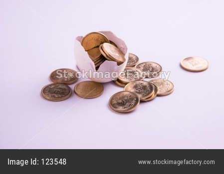 indian five rupee golden coins emerging from cracked egg, isolated over white background