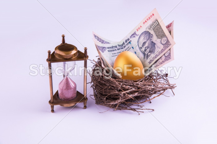 Hourglass With Golden Egg And Indian Money Or Paper Currency