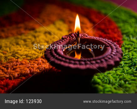 Diwali Diya over Rangoli made using Colourful Rice grains