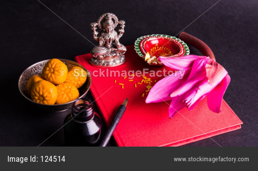 Shubha Labh written over Red accounting note book / bahi khata with goddess Laxmi , diya and sweets
