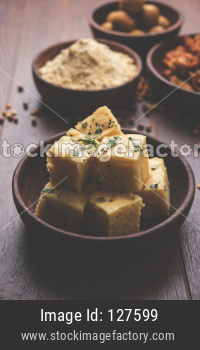 Chick pea flour or Besan powder in a ceramic or wooden bowl along with Gujrati Dhokla snack, onion bajji or bhaji and sweet ladd