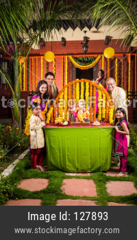 Happy Indian Family Celebrating Ganesh Festival or Chaturthi - Welcoming or performing Pooja and eating sweets in traditional we
