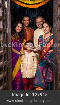 Happy Indian family entering house with puja thali through old antique door - Griha Pravesh