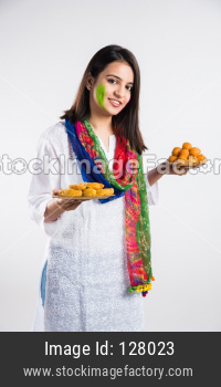 Indian girl celebrating holi with sweets