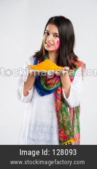 indian people celebrating Holi, festival of colours with plates full of colours and faces painted, happiness concept, standing i