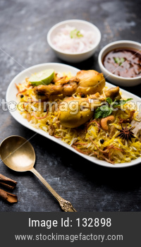 Chicken biryani in bowl over moody background